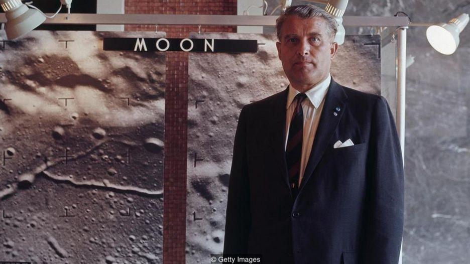 Wernher von Braun posa para foto em frente a painel mostrando a superfície lunar