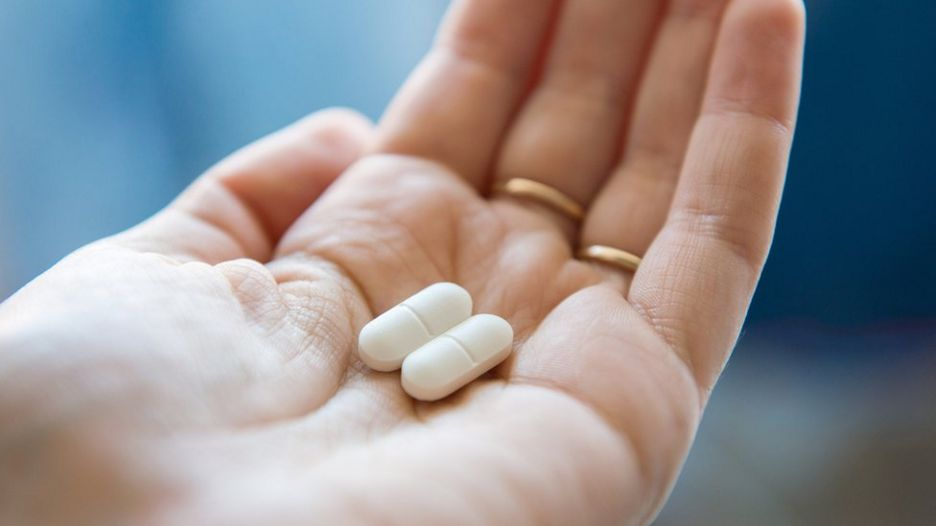 Two pills in the palm of someone's hand