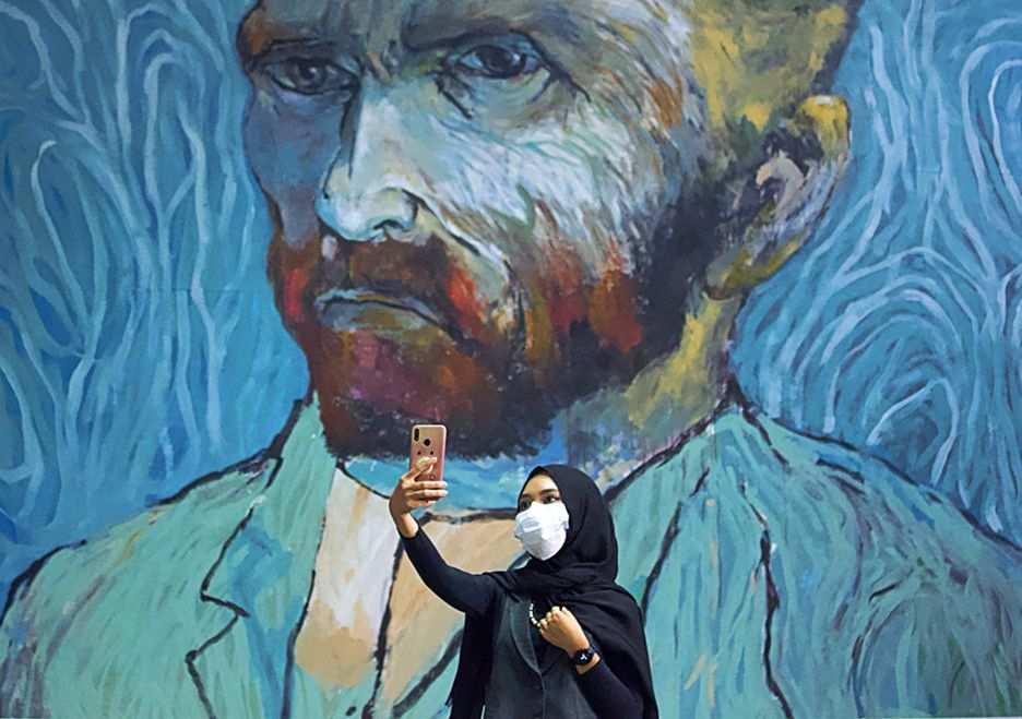 A woman takes a selfie with a large mural of Van Gogh