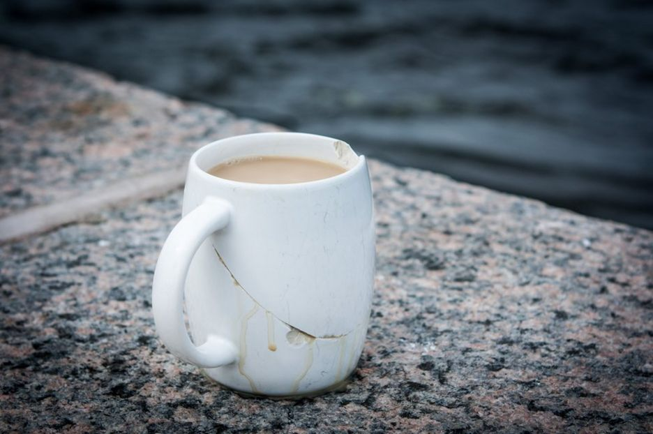A cracked coffee cup next to the river