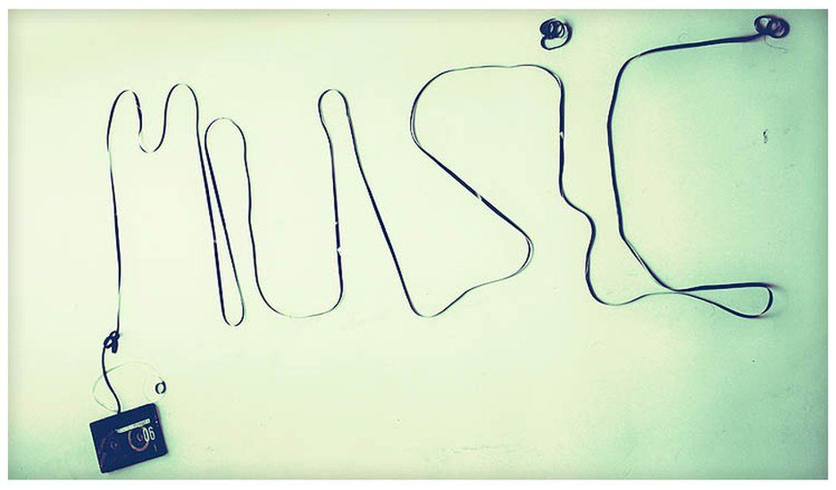 A piece of cassette tape spells out the word 'music'