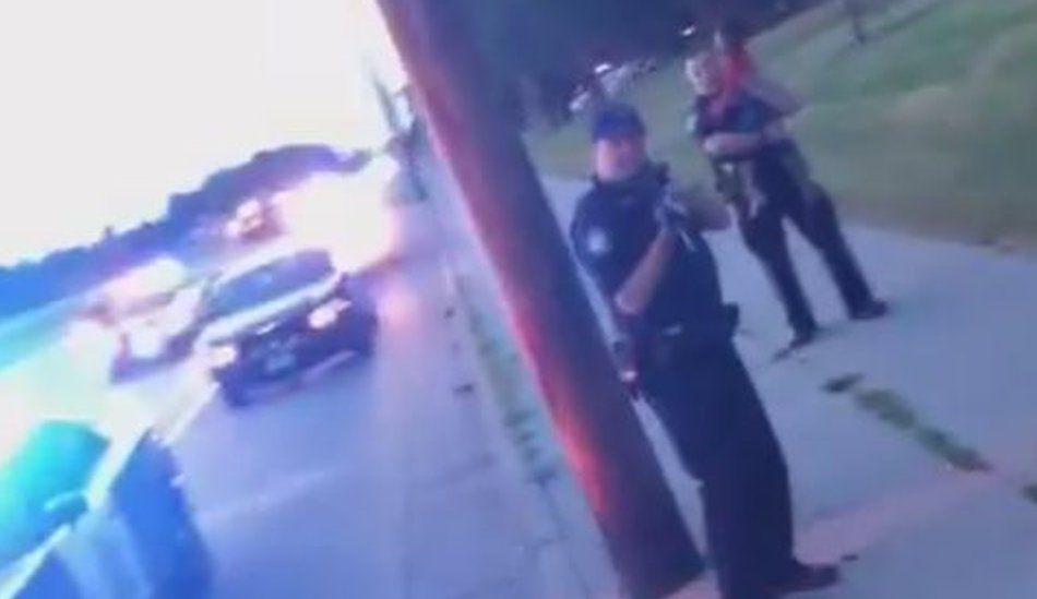 Still from Facebook Live feed shows police car and police officer near it pointing gun at the woman - another police officer is behind him, holding a young girl - July 2016