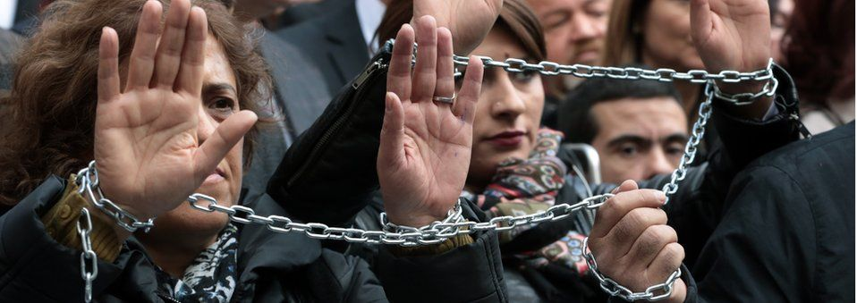 Journalists with chained hands protest against the jailing of opposition Cumhuriyet newspaper's editor-in-chief Can Dundar and Ankara representative Erdem Gul