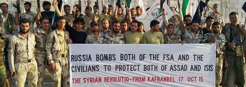 Members of the Fursan al-Haq Syrian rebel brigade hold up a banner criticising Russia's air campaign in Syria (17 October 2015)