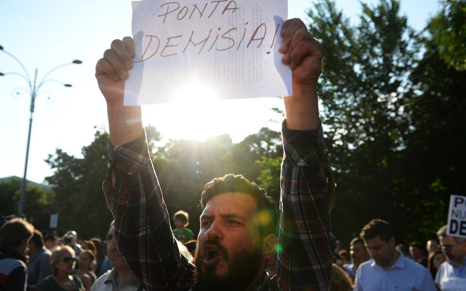A man holds a placard reading in Romanian 'Ponta, RESIGN!' during a protest asking the resignation of Romanian Mr Ponta next to Romanian Government headquarters in Bucharest on June 5, 2015.