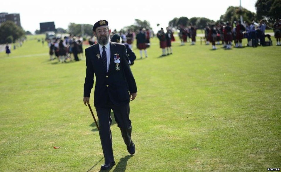 A veteran arrives at a parade in Folkestone, Kent, to mark Monday's anniversary