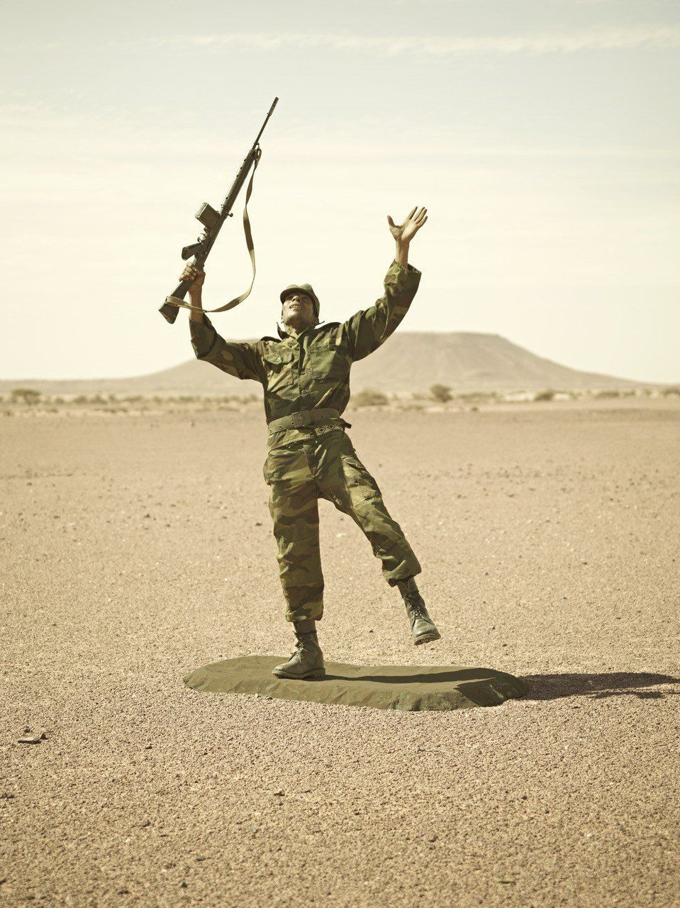 A soldier outdoors posing with his hand and gun towards the sky