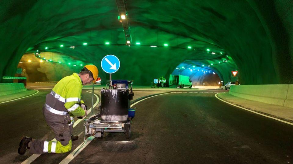 A worker paints road markings inside the tunnel