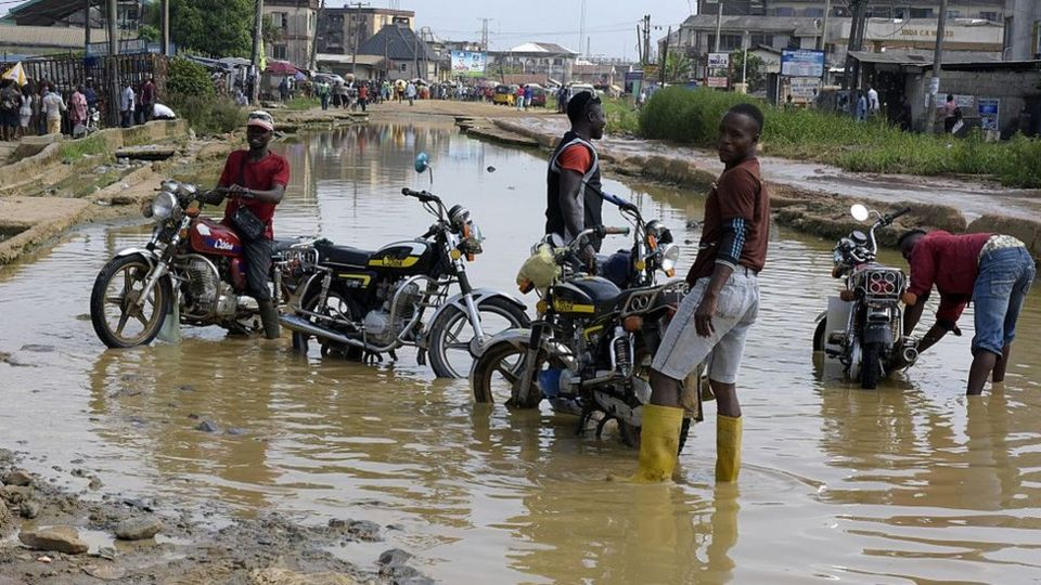 Motorcyclists wash their bikes in the flooded and dilapidated Port Harcourt-Aba highway abandoned by maintenance agencies resulting in an ongoing pro-Biafra protesters agitating for the breakaway of a Biafran state, on November 18, 2015