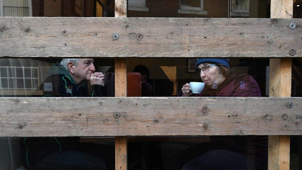 A couple sit inside a boarded-up coffee shop ahead of the annual Royal Shrovetide football match