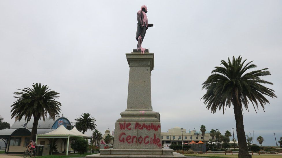 """A statue of Captain Cook covered in pink paint and spray-painted with the words: """"We remember genocide"""""""