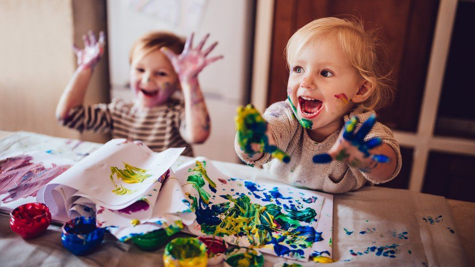 Children painting on kitchen table