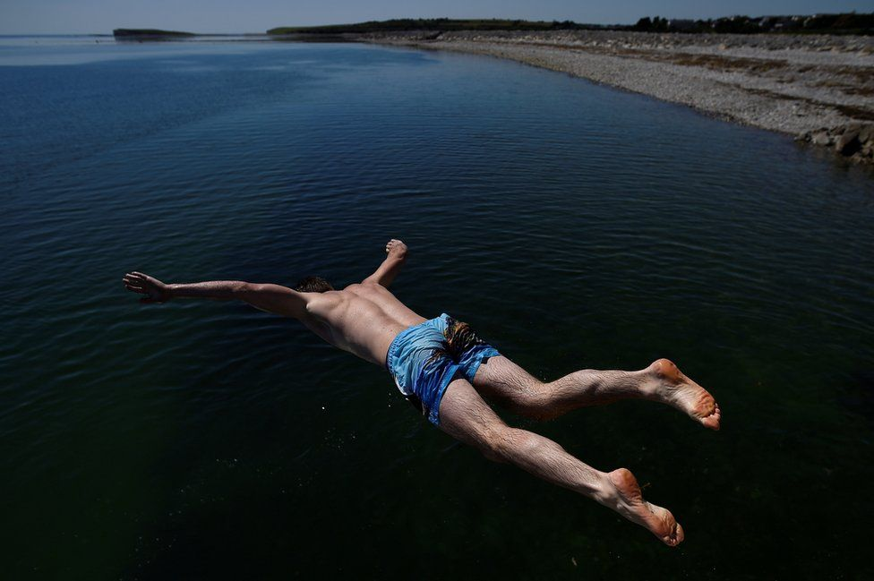 A man jumps into the sea at Salthill beach during sunny weather in Galway, Ireland, 26 June 2018.