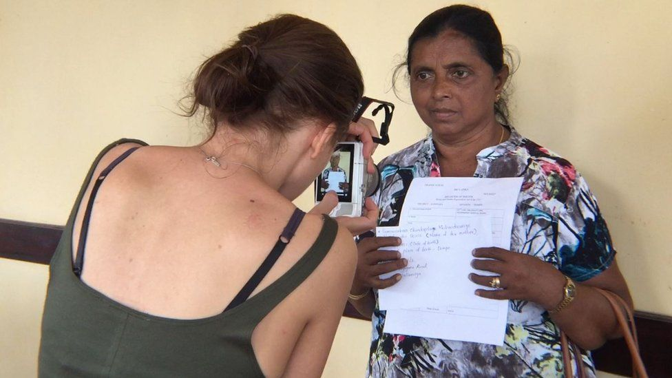 A woman photographs an estranged mother holding up her details for Facebook