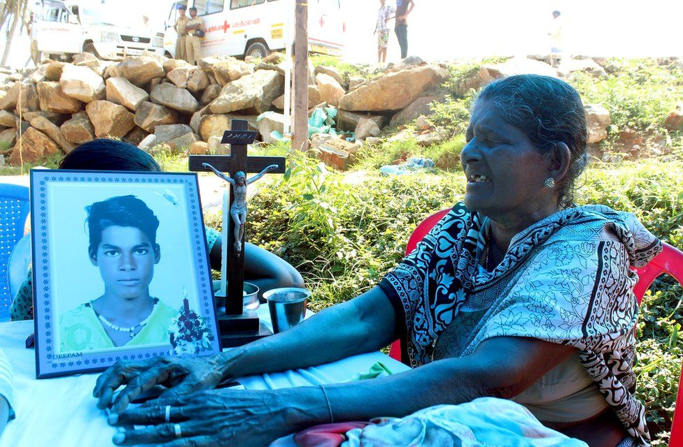 Susie Vincent is crying next to a photograph of her 15-year-old grandson, Vineesh.