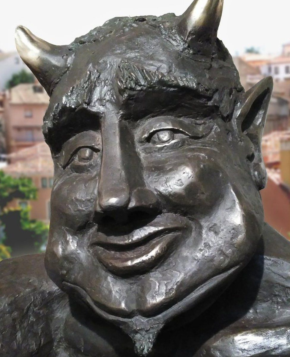 Close-up of the Satan sculpture with smiling face