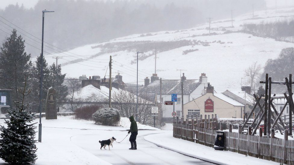 A man walks his dog through snow in Overwater, Cumbria, as five weather warnings are in place as heavy rain and snow blight swathes of the country on Easter Monday.