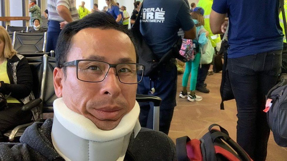 A man takes a selfie wearing a neck brace, with fire department and others behind