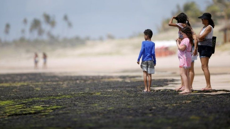 People look at oil spilled on a beach in Bahia state, Brazil. Photo: 12 October 2019