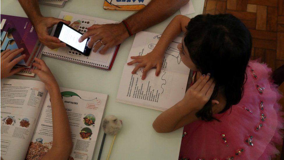 Em foto tirada de cima, duas crianças com seus livros didáticos e um adulto mostrando algo no celular