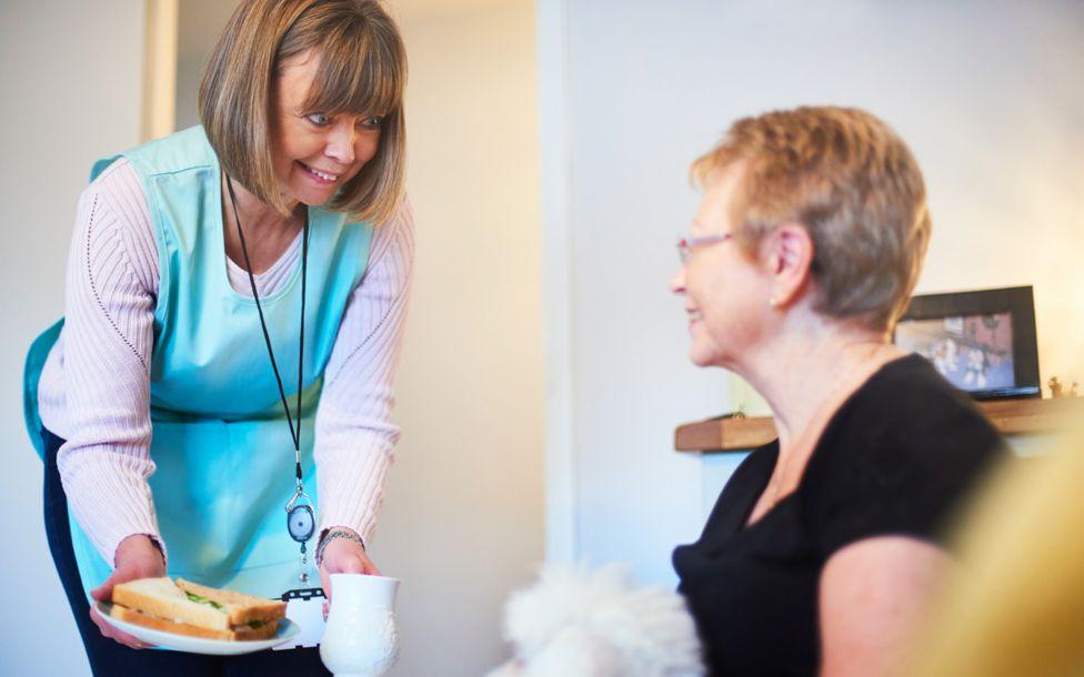 Asistenta social le ofrece un emparedado a una mujer mayor