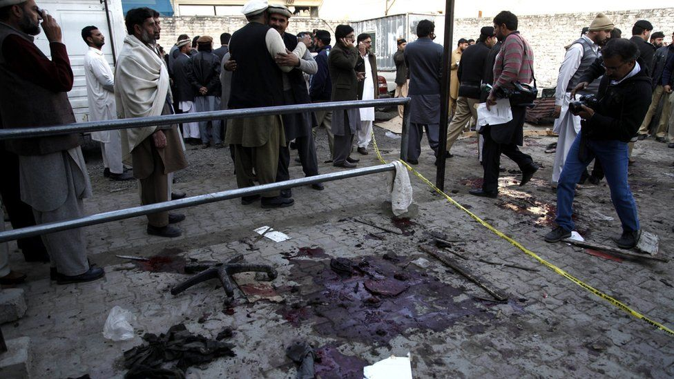 People stand at the site of a suicide attack that targeted National Database and Registration Authority (Nadra) office in Mardan, Pakistan, 29 December 2015