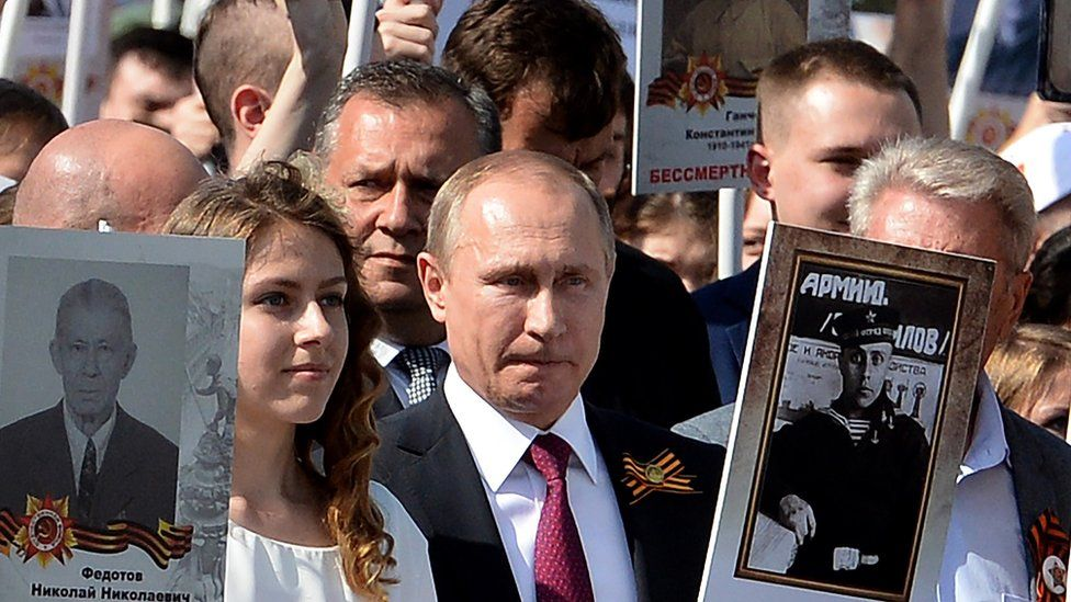 Russian President Vladimir Putin (C) carries a portrait of his father Vladimir as he takes part in the Immortal Regiment march in Moscow on May 9, 2016