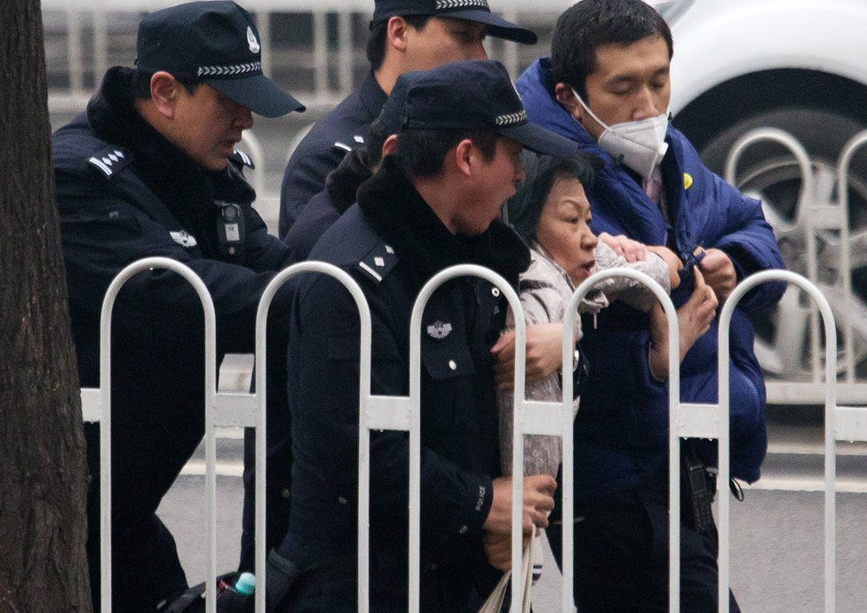 """Police officers take away a supporter of rights lawyer Pu Zhiqiang near the Beijing Second Intermediate People""""s Court during his trial in Beijing, Monday, 14 December 2015"""
