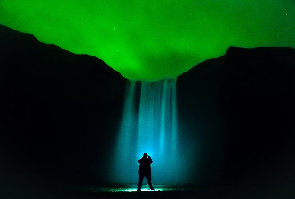 A waterfall is illuminated under the aurora lit sky