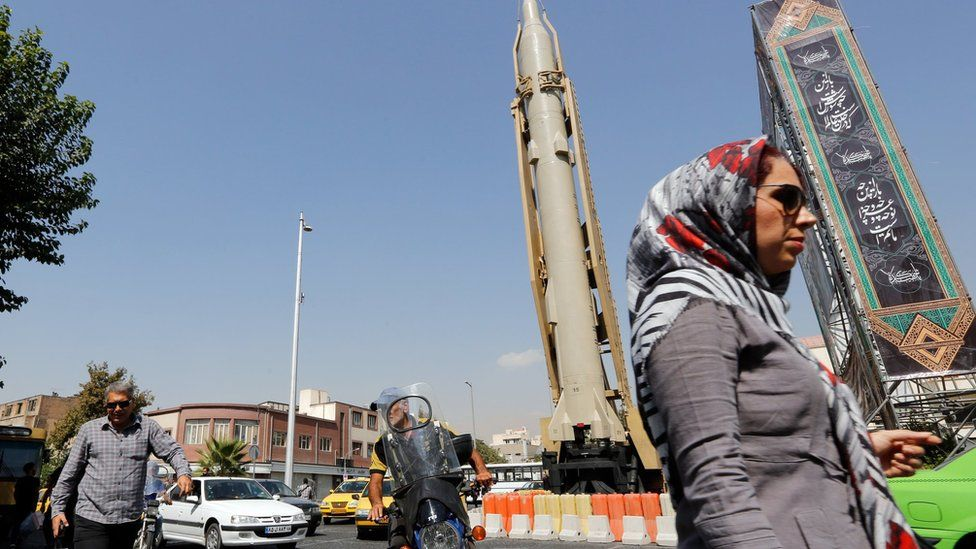 A woman walks past a Shahab-3 ballistic missile and launcher on a street in Tehran, Iran, during Defence Week (26 September 2019)