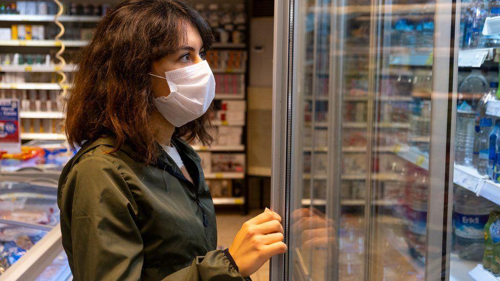 Woman looks into shop shelf