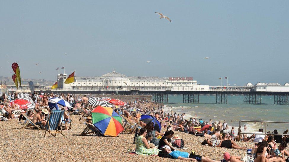 People sunbathe on the beach at Brighton