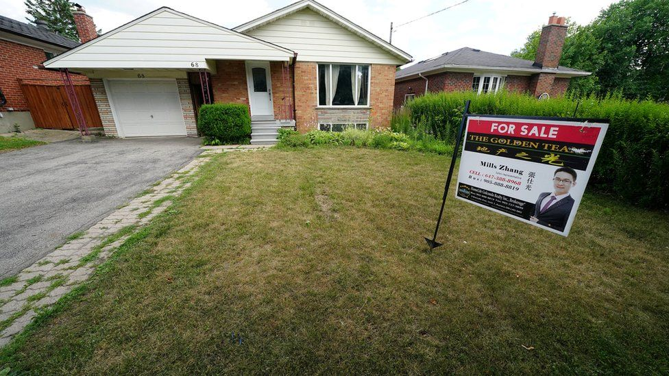 """""""For Sale"""" sign is pictured in the front yard of a house in Toronto, Ontario, Canada"""