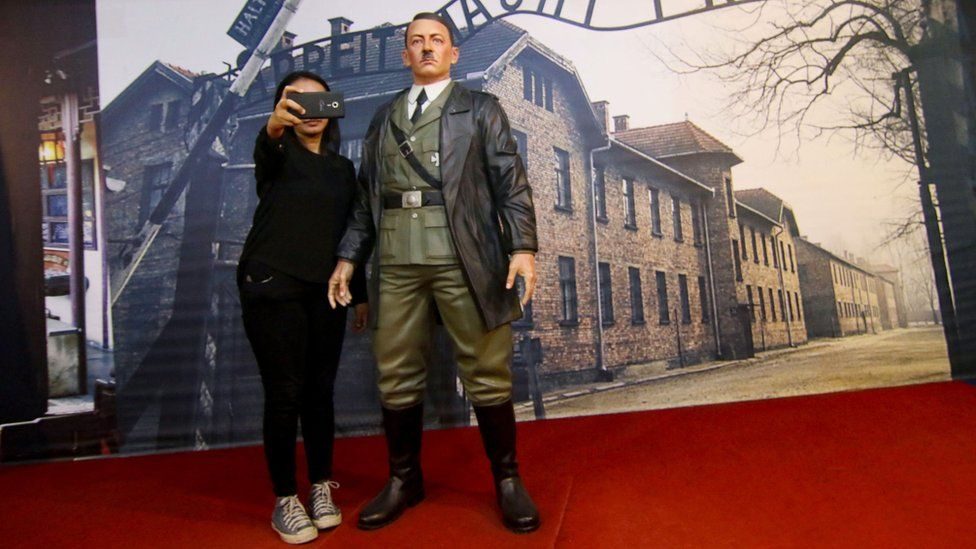 A woman poses with Adolf Hitler waxwork in an Indonesian museum
