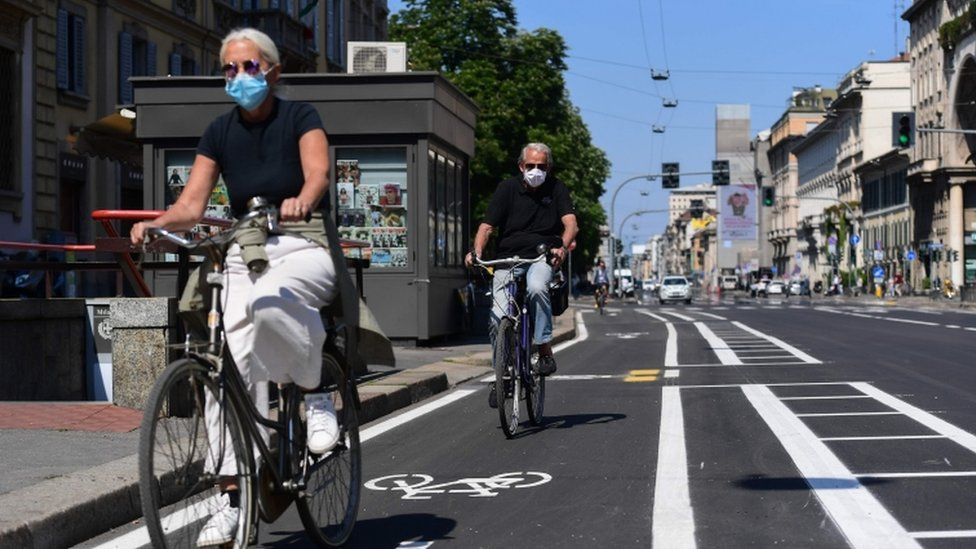 People ride their bicycle through a bike lane in central Milan on 4 May