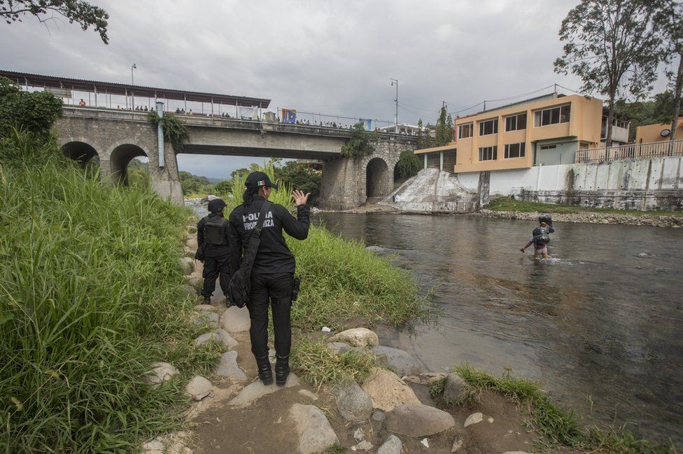 Sgt Lopez beckons to a man in the river
