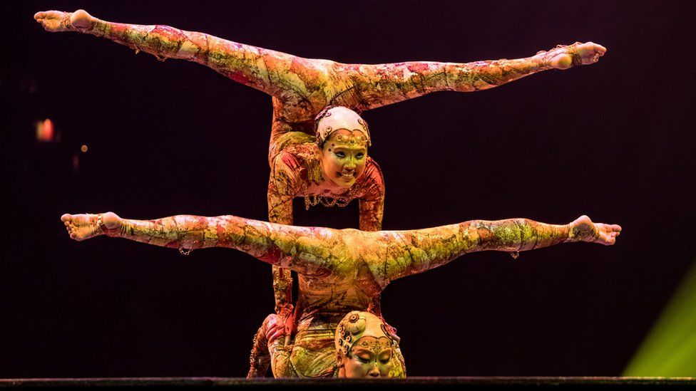 Two Cirque du Soleil acrobats in colourful outfits balance with their legs above their heads