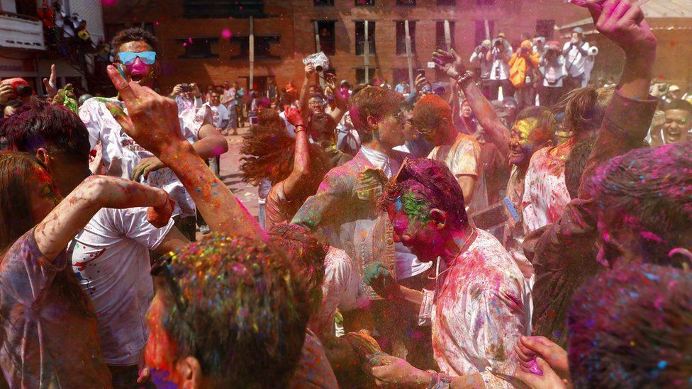 Nepalese people painted with coloured powder dance in Kathmandu