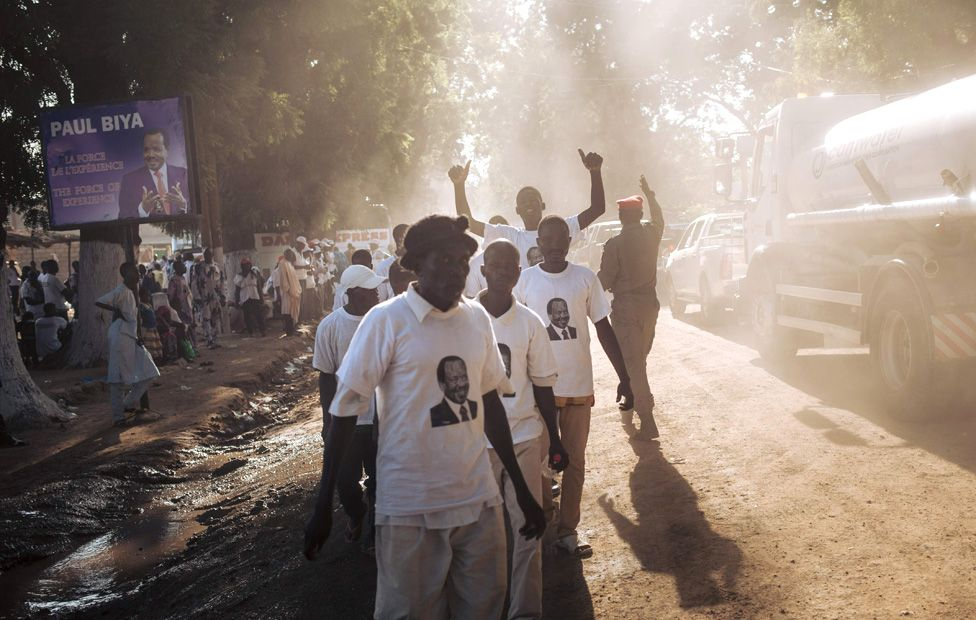 In this photograph taken on September 29, 2018, supporters of the President Paul Biya walk in a street of Maroua, Far North region of Cameroon, after sn electoral meeting he held in the city.