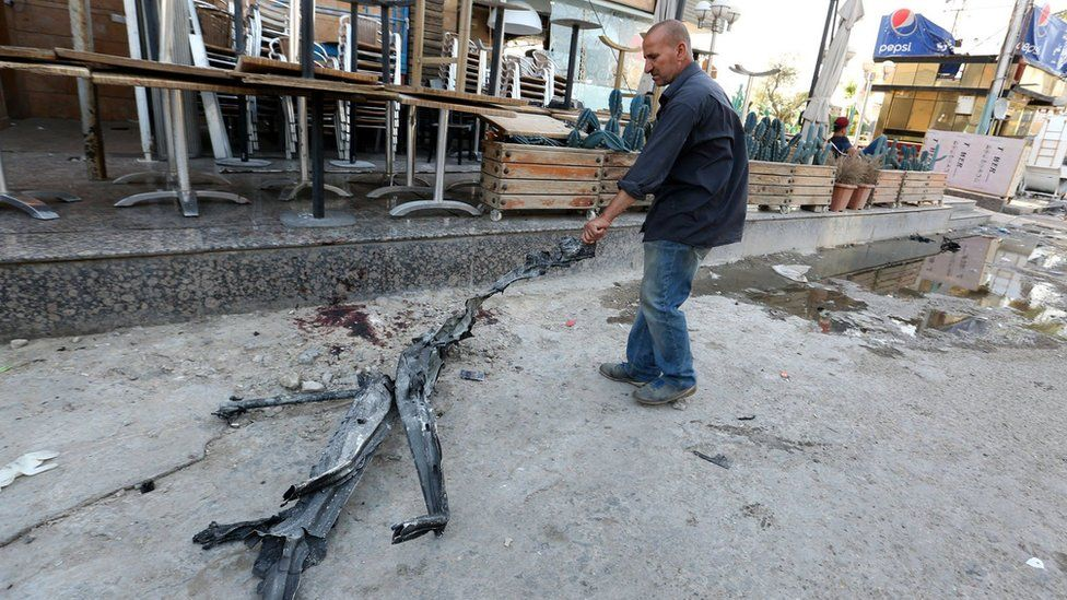 An Iraqi civilian drags a piece of debris at the site of bombing at Al-Faqma ice cream shop in Karrada, Baghdad (30 May 2017)