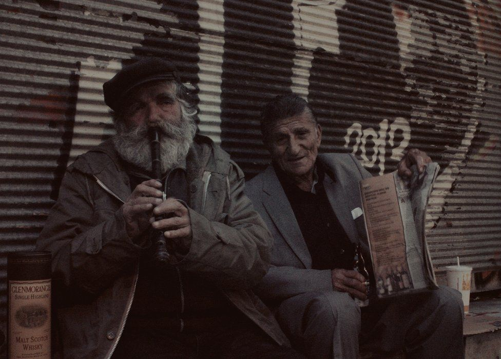 Two older men sitting on the street, one with a pipe in his mouth