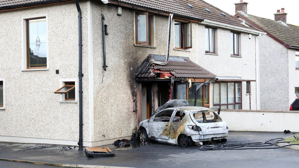 Burned car outside the house