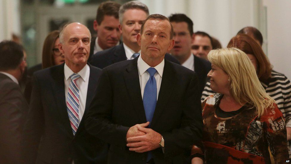 Australian Prime Minister Tony Abbott, centre, leaves the Australian Liberal Party meeting in which he lost the party leadership at Parliament House in Canberra, Monday, Sept. 14, 2015