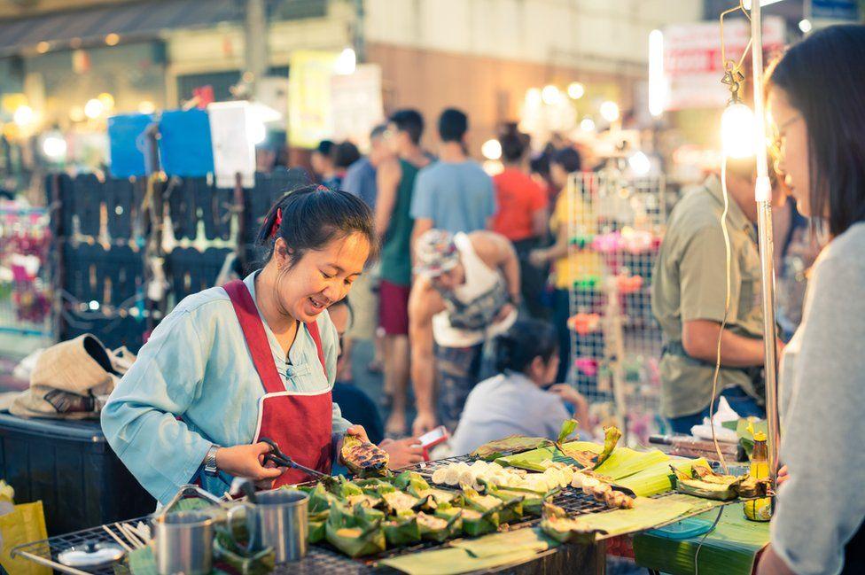 A woman serves roasted banana snacks at Wua Lai Road street market in Chiang Mai, Thailand