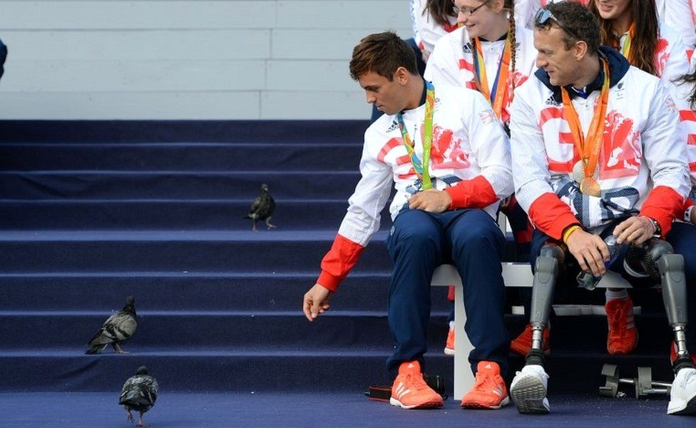 Tom Daley reacts to pigeons on stage alongside Richard Whitehead