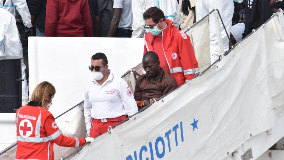 """A migrant is helped off the coast guard ship """"Diciotti"""" after arriving at Catania Port, Italy, 13 June 2018"""