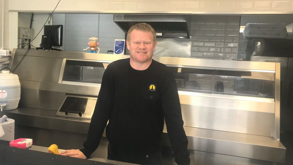 President of the National Federation of Fish Friers, behind the counter of a fish and chip shop