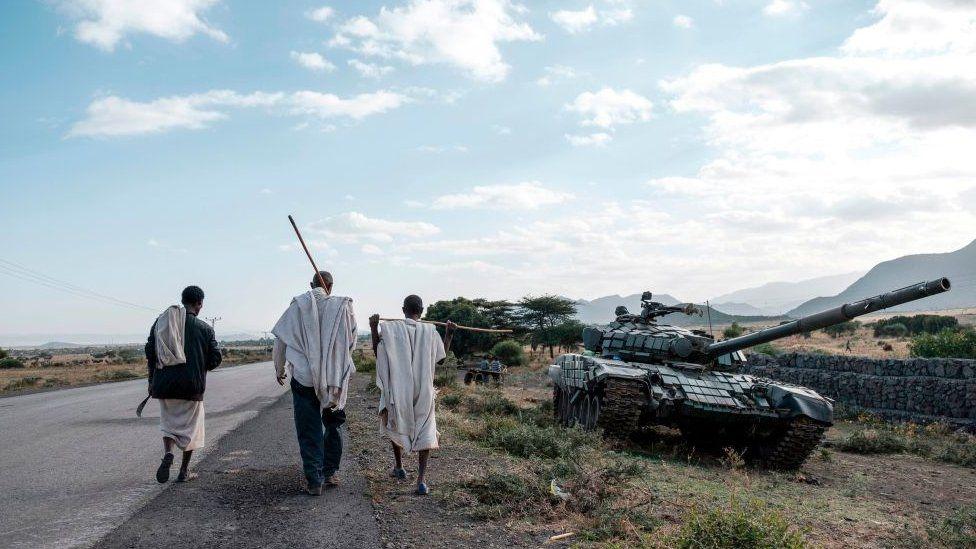 People walking past a tank in Tigray, Ethiopia - November 2020