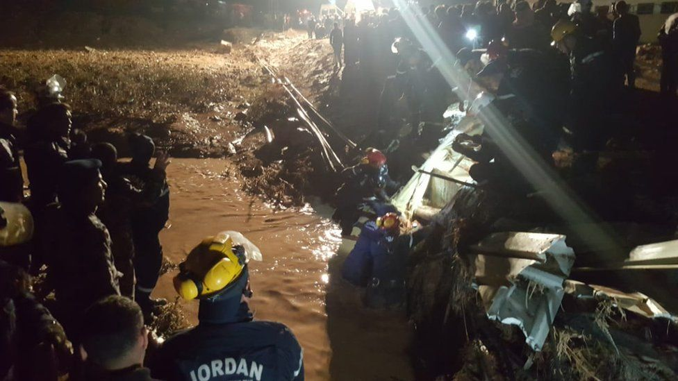 Rescue workers in Jordan wade through debris in a flooded area overnight