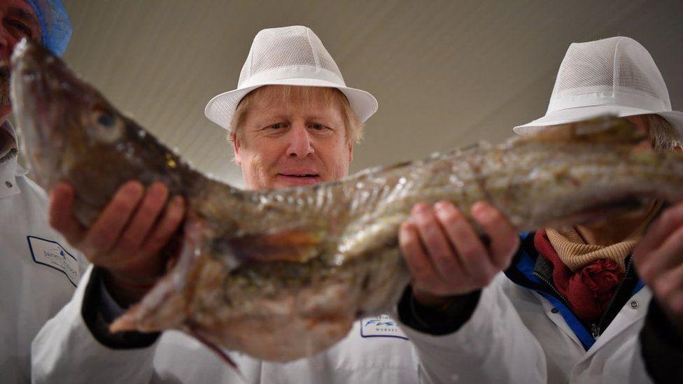 UK Prime Minister Boris Johnson holding a large fish